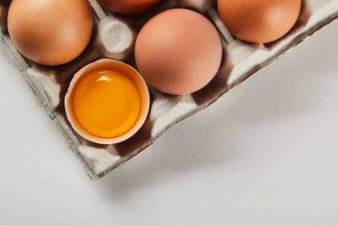Top view of broken eggshell with yellow yolk near eggs in carton box stock vector