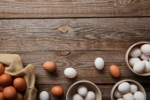 Photo  top view of chicken eggs in bowls on wooden table with cloth