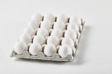 Chicken eggs in carton box on white surface stock vector