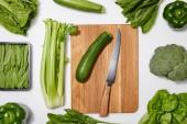 vista dallalto delle verdure verdi e del tagliere di legno con coltello su sfondo bianco