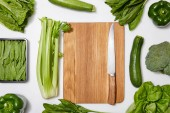 top view of green vegetables around wooden chopping board with knife on white background