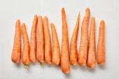 top view of fresh carrots in row on white background