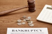 selective focus of bankruptcy form, gavel, calculator and coins on brown wooden table