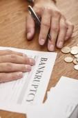 částečný pohled na podnikatele, který vyplňuje konkursní formu u dřevěného stolu s mincemi