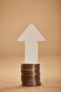 stack of coins with white arrow upwards, financial growth concept