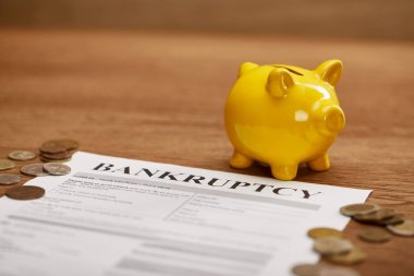 selective focus of bankruptcy form, coins, yellow piggy bank on wooden table
