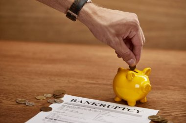 cropped view of man putting coin in yellow piggy bank near bankruptcy form