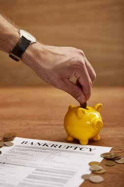 partial view of man putting coin in yellow piggy bank near bankruptcy form