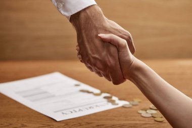 selective focus of man and woman shaking hands near bankruptcy form and coins