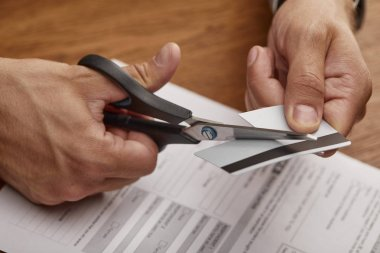cropped view of businessman cutting credit card with scissors at wooden table