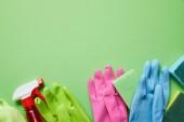 pohled na barevný hadr, gumové rukavice, sprej a houbičky na zeleném pozadí