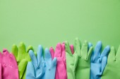 Photo top view of colorful and bright rubber gloves on green background