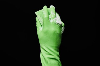cropped view of man in green rubber glove holding sponge isolated on black