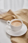 close up view of coffee in white cup on saucer near beige napkin