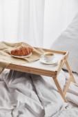 káva a croissant podávané na dřevěném tácku na bílém lůžku s polštářem