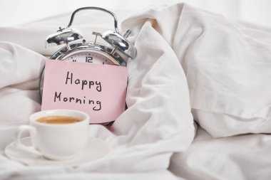Coffee in white cup near silver alarm clock with happy morning lettering on sticky note in bed stock vector