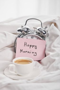 Coffee in white cup on saucer near silver alarm clock with happy morning lettering on sticky note in bed stock vector