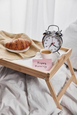 Silver alarm clock, sticky note with happy morning lettering, coffee and croissant on wooden tray on white bedding stock vector