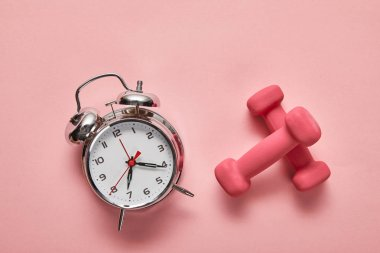 top view of silver alarm clock and pink dumbbells on pink background