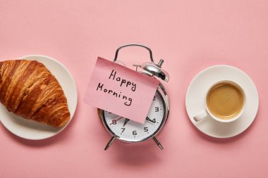 Top view of alarm clock with happy morning lettering on sticky note near coffee and croissant on pink background stock vector