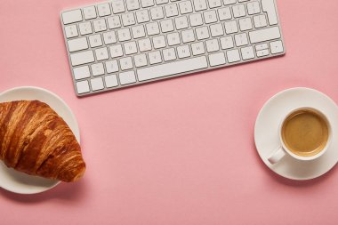 Top view of computer keyboard near coffee and croissant on pink background stock vector