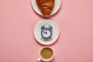 flat lay with coffee cup, toy alarm clock and croissant on plate on pink background