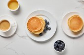 top view of bowls with blueberries and honey near plates with pancakes and cup of coffee