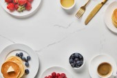 top view of tasty breakfast with pancakes, honey, different kinds of berries and cup of coffee