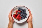 oříznutý pohled člověka, který drží velkou misku s chutnými jahodami a modrými plody