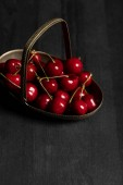 red delicious cherries in metal basket on wooden dark table