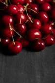 red delicious cherries scattered on wooden dark table
