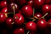 close up view of red tasty and ripe cherries