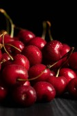 selective focus of red delicious and ripe cherries with water drops isolated on black