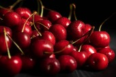 selective focus of red ripe cherries with water drops isolated on black