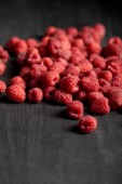 Photo selective focus of delicious ripe raspberries scattered on wooden table