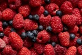 Photo close up view of fresh delicious ripe mixed raspberries and blueberries