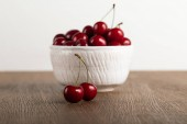 selective focus of red cherries in bowl on wooden table isolated on white