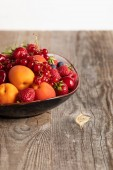 Photo close up view of plate with mixed delicious ripe berries on wooden table isolated on white