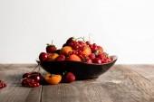 Fotografie talíř se smíšenými lahodnou zralými plody na dřevěném stole izolovaným na bílém