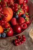 close up view of ripe seasonal berries and apricots on plate on wooden table