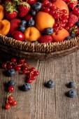 közeli kilátás az érett bogyósgyümölcsösbe és sárgabarackba a fonott kosárban, fa asztalon