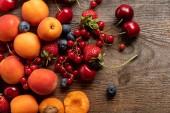 az érett, ízletes friss bogyós gyümölcsök és a sárgabarack, fából készült asztal felülnézete