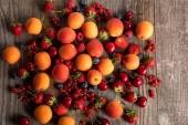 Nejlepší pohled na zralé lahodné čerstvé bobule a meruňky roztroušené na dřevěném stole