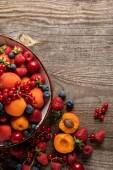 az érett finom bogyós gyümölcsök és a sárgabarackok felsõ nézete a falon, másolási hellyel