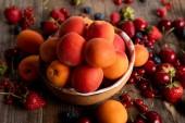 zblízka pohled na zralé delikátní sezonní bobule roztroušené kolem mísy s meruňkami na dřevěném stole