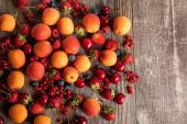 top view of ripe delicious seasonal berries scattered with fresh apricots on wooden table