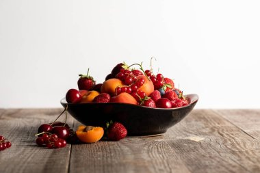 plate with mixed delicious ripe berries on wooden table isolated on white