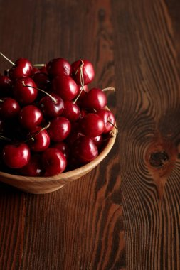 red delicious cherries in wooden bowl on wooden brown table