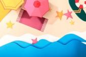 Draufsicht auf Papierstrand mit Seesternen, Handtüchern, Sonnenschirmen und Surfbrett mit Rettungsring auf Sand am Meer