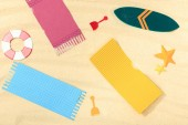 top view of paper beach with surfboard and towels on textured sand